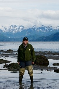 a park ranger stands in tidal water in waders with mountains in the background
