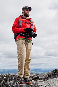 man in outdoor attire standing atop a mountain