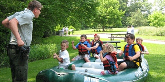 Adult ranger giving a group of kids instruction on land in a raft.