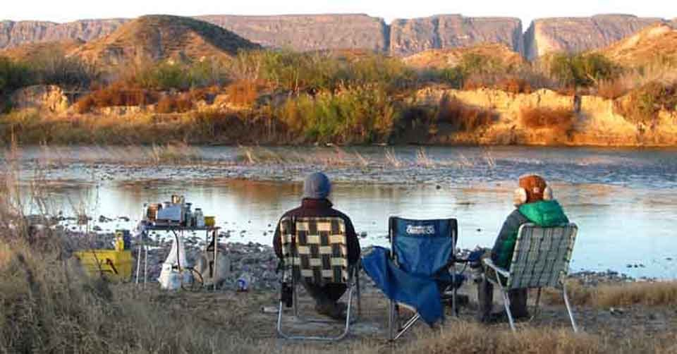 People sitting alongside the Rio Grande River in a peaceful setting.