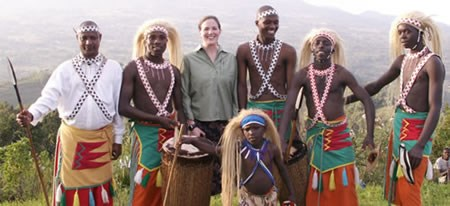 An NPS Concessions Specialist with a group of Rwanda dancers who are dressed in colorful native garb.