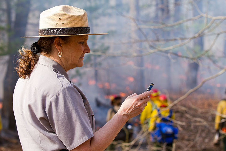 ranger using a smartphone to update the public about a wildland fire