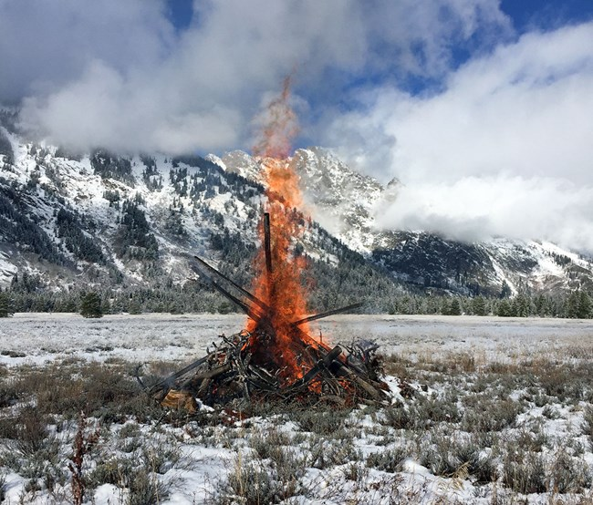 slash pile burning in the sunny snowy scenic mountains at Grand Teton National Park