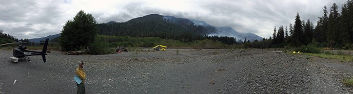 A helicopter sits on a gravel bar with a firefighter nearby and tents in the distance.