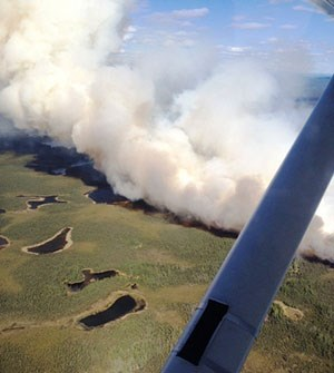 Aerial view of smoke and flames blackening tundra.