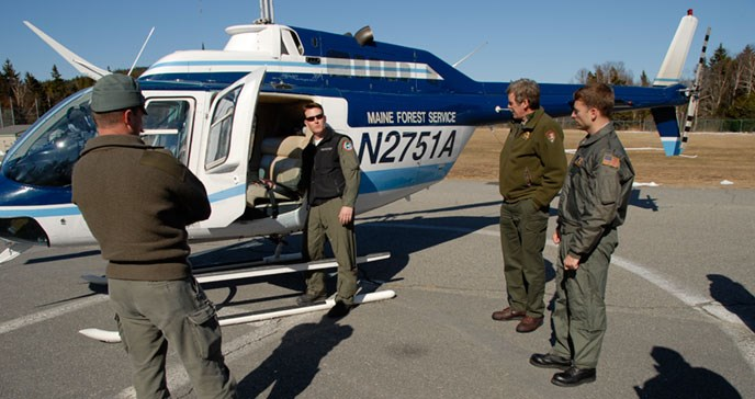 Three men stand and listen to a man pointing at something in a helicopter.