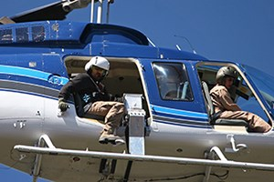 A man leans out of a helicopter looking at the ground below with a silver machine next to him.