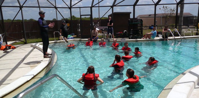 A group of students stands in a pool with life vests listening to a person talk from the edge of the pool.