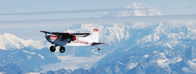 Fixed wing single engine aircraft flying under blue skies and above snowy mountains.