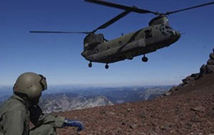 A person in a green flight suit hunches on the ground while a helicopter takes off nearby in a rocky mountainous area.
