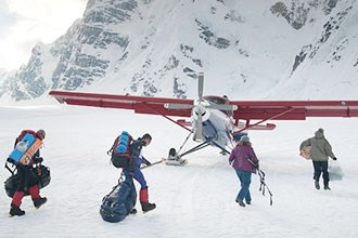 A group carrying packs walks toward an airplane on a glacier with snowy mountains in the background.