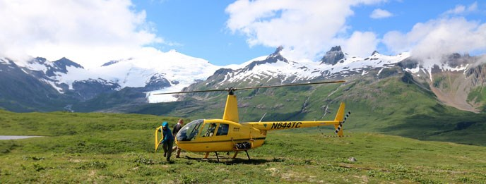 A person carries the door of a helicopter near a helicopter on tundra with mountain backdrop.