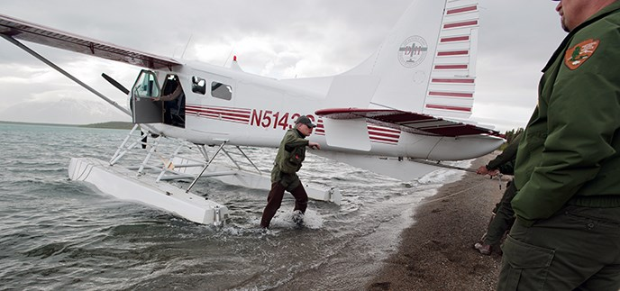 A man in NPS uniform wades from a floatplane to shore
