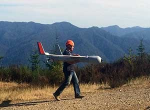 A man in a helmet carries an aircraft in his arms on a dirt trail.