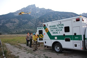 Rangers and crew members load a patient into an ambulance while a helicopter flies away.