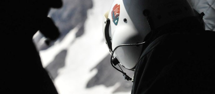 person in a flight helmet looks out at a snowy mountainous landscape from a helicopter.