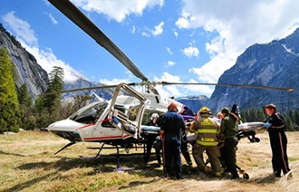 A group loads a stretcher into a helicopter in a meadow surrounded by mountains.