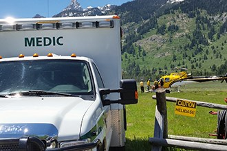 An ambulance waits at the entrance to a helibase while crew members unload a patient from a helicopter.