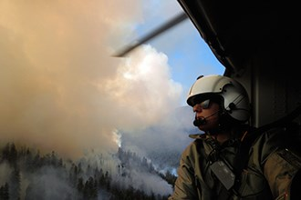 A woman in a flight helmet looks out the door of a helicopter on mountain filled with smoke.