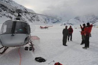 group stands outside of helicopter on snowy field with an airplane in the background