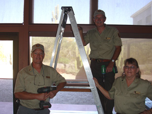 Volunteers pose after hanging new blinds in the visitor center