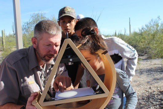 Park Ranger assists students view the sun through a solar scope