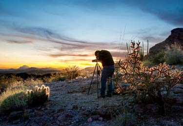 A photographer stands in the desert awaiting the sunset.
