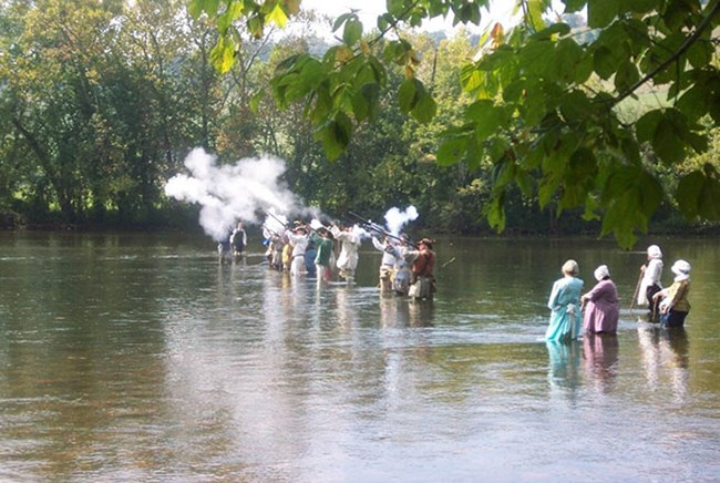 People in period costume firing muskets while standing in the Watauga River