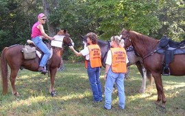 Volunteer Horse Patrol members greet a rider on a trail