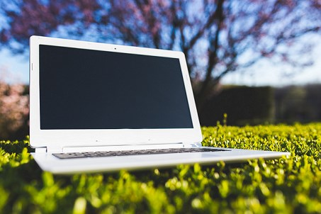 a white laptop sitting in the grass