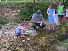 Bill O'Donnell in creek with kids