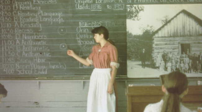 School teacher dress is period style clothing at chalkboard at school