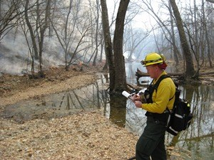 a firefighter checks notes next to a smoking line of fire in the woods