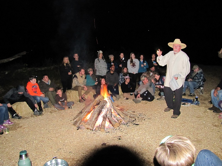 story teller in front of a group around a bonfire