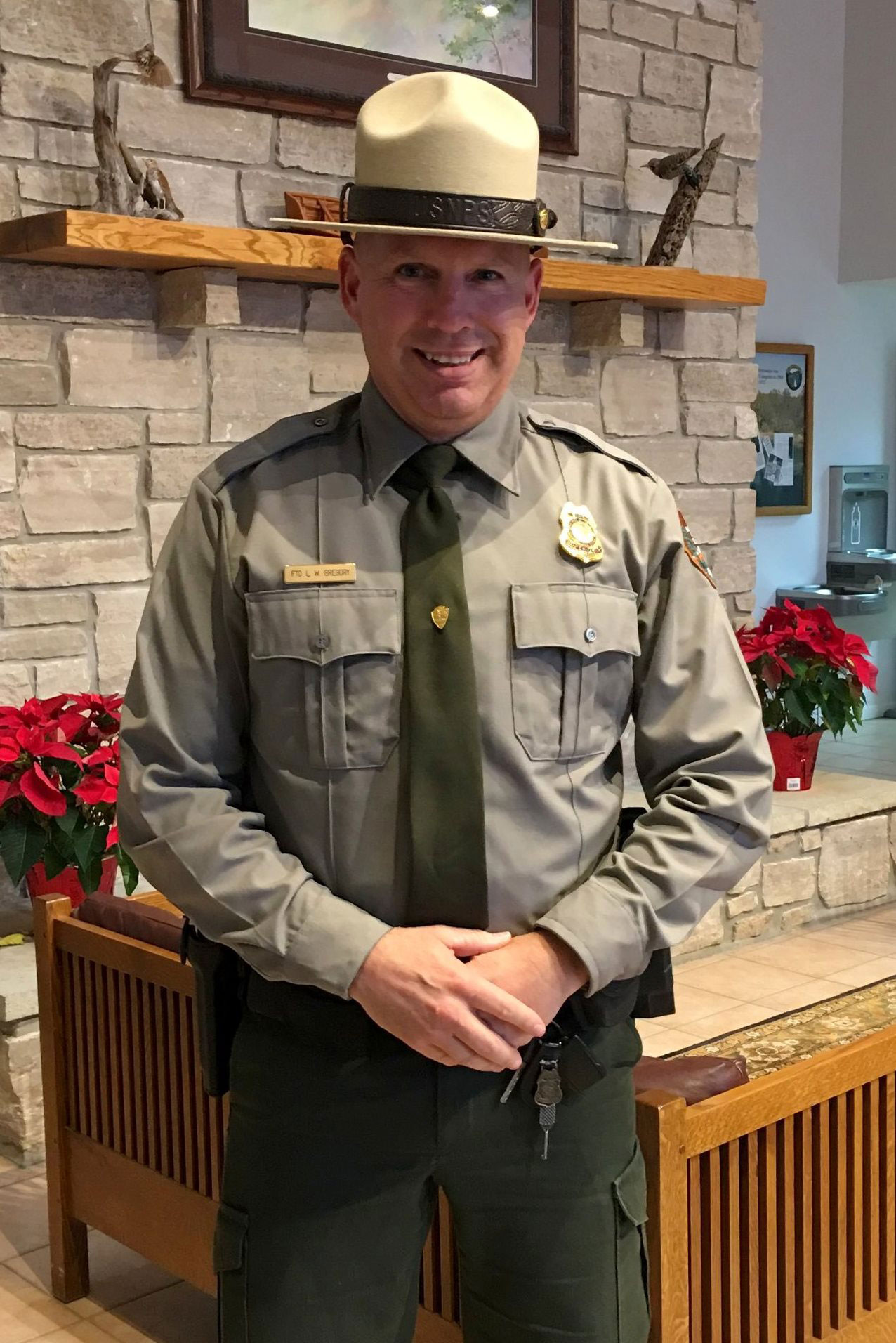 Chief Ranger Lindel Gregory stands in front of the mantle at Park Headquarters