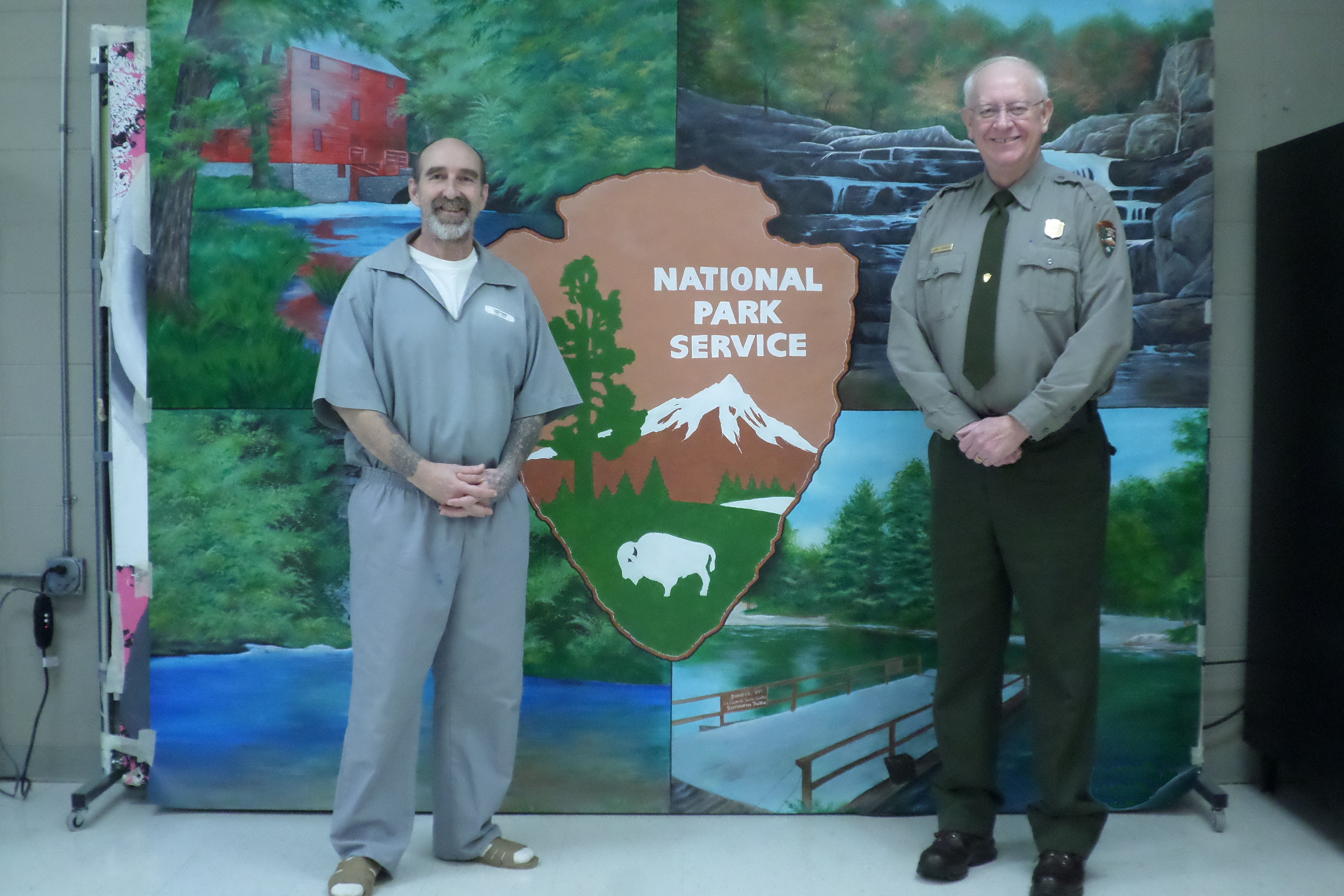 artist and park superintendent stand in front of canvas with painting of red mill and springs