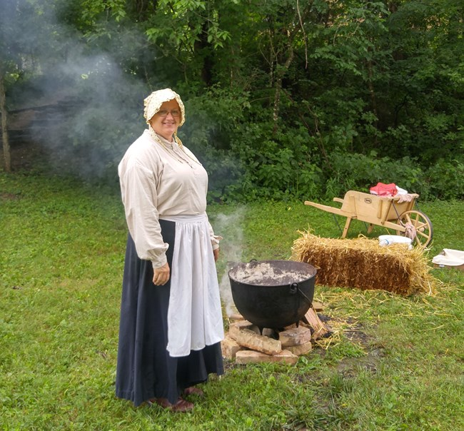lady in pioneer dress and bonnet stirs lye soap in kettle