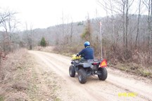 man on atv riding on dirt road