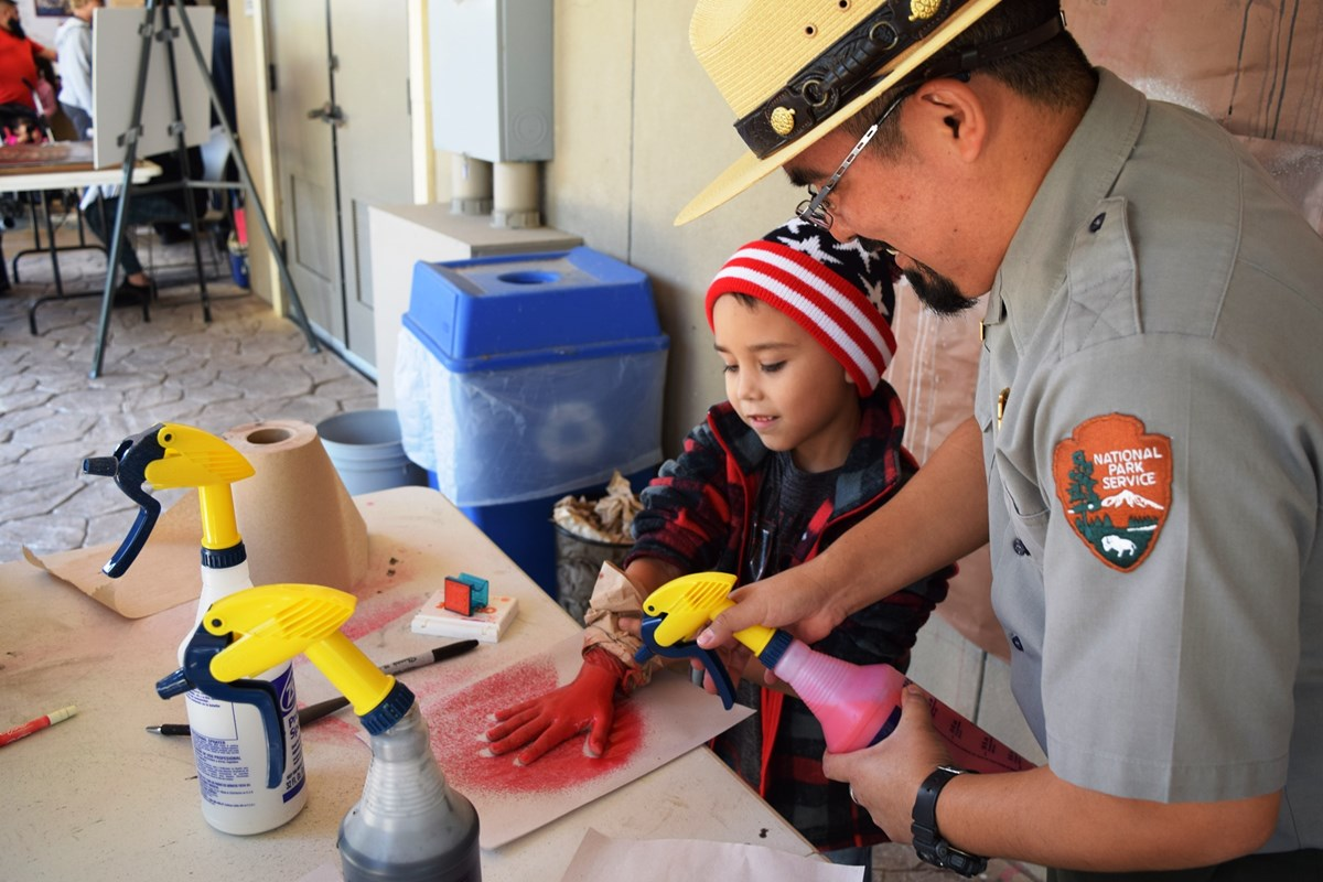 A Ranger helps a boy with a cave art activity