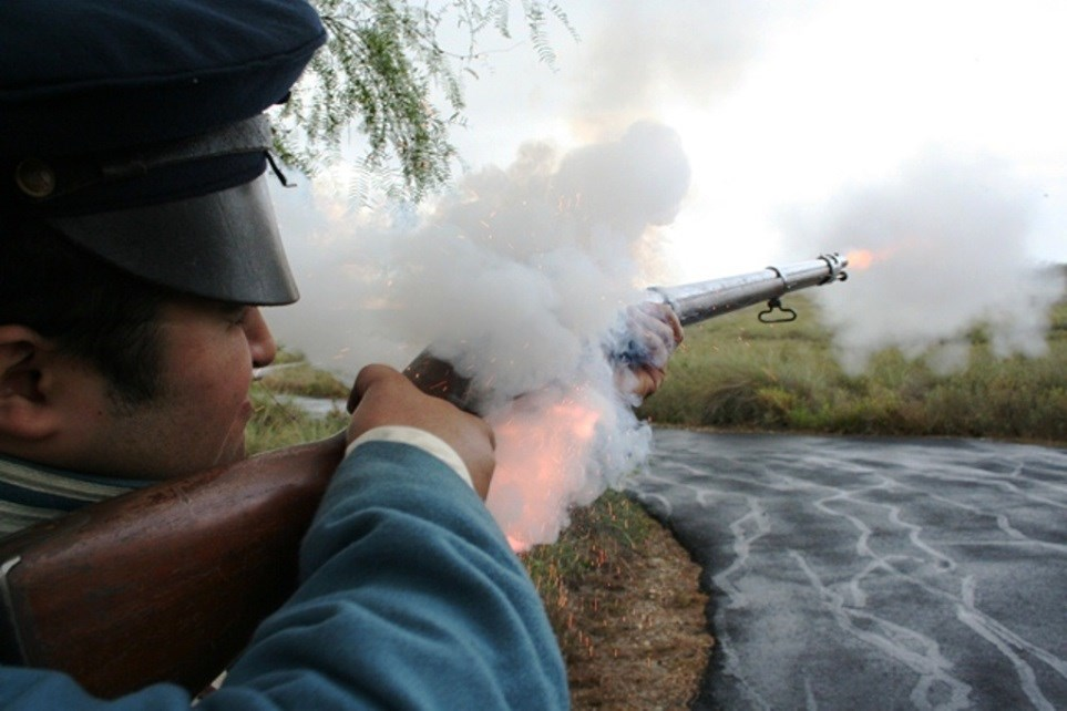 Sparks and flames shoot out as a living historian fires a musket.