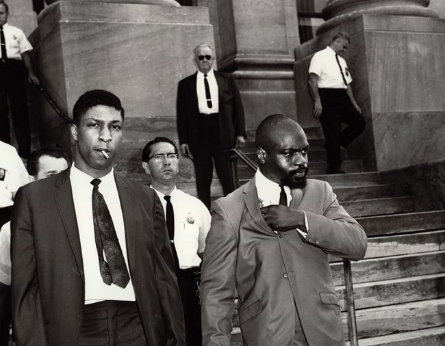 "Rubin ""Hurricane"" Carter exiting court house with 5 police officers. To Rubin Carter's right is John Artis."