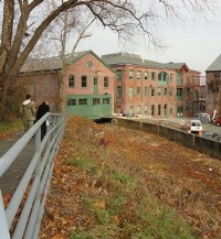 Visitors walking along the Upper Raceway behind some of the the Rogers Locomotive Works buildings.
