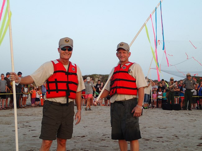 Two volunteers for the sea turtle division wearing life vests and hold flags smile at the camera