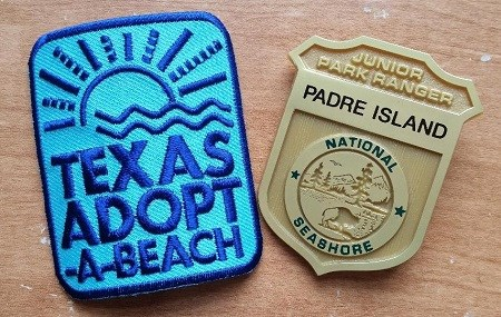 Blue Texas Adopt-a-Beach patch and gold plastic junior ranger badge