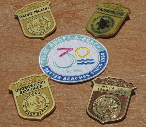 Four gold Junior Ranger badges and an Adopt-A-Beach patch in the center
