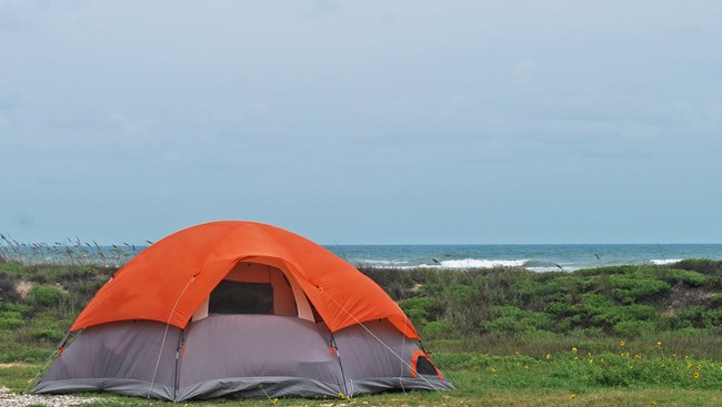 Orange tent at site adjacent to the beach and blue waters of the Gulf of Mexico.