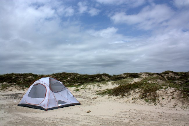Photo of a white tent on the beach with the dunes and a blue sky and clouds in the background.
