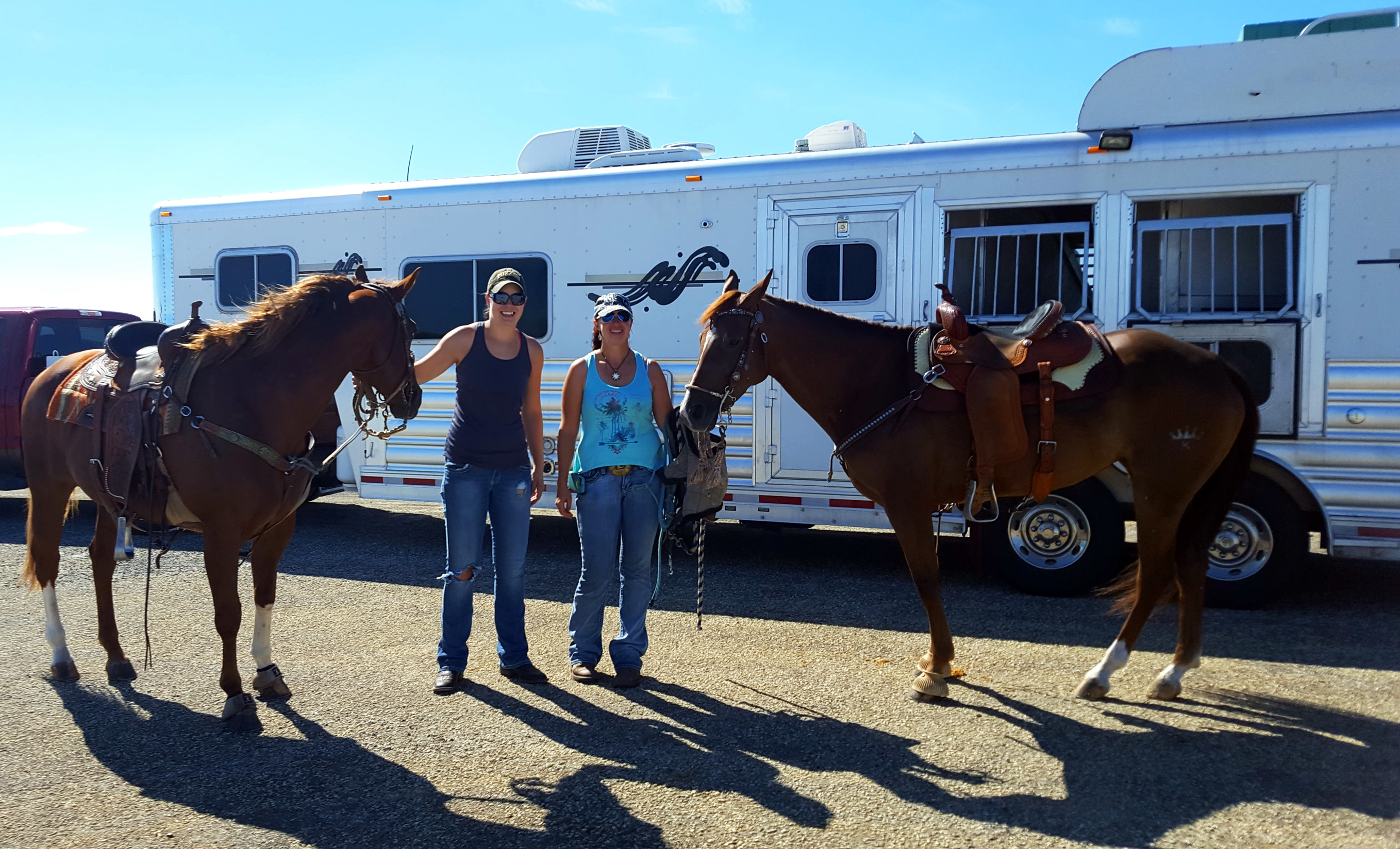 Visitors and their horses in front of their trailer
