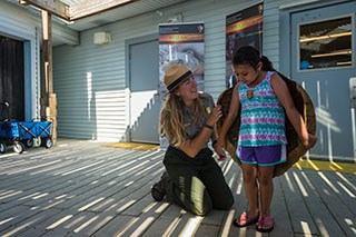 A ranger kneels helping a young girl hold a sea turtle shell on her back.