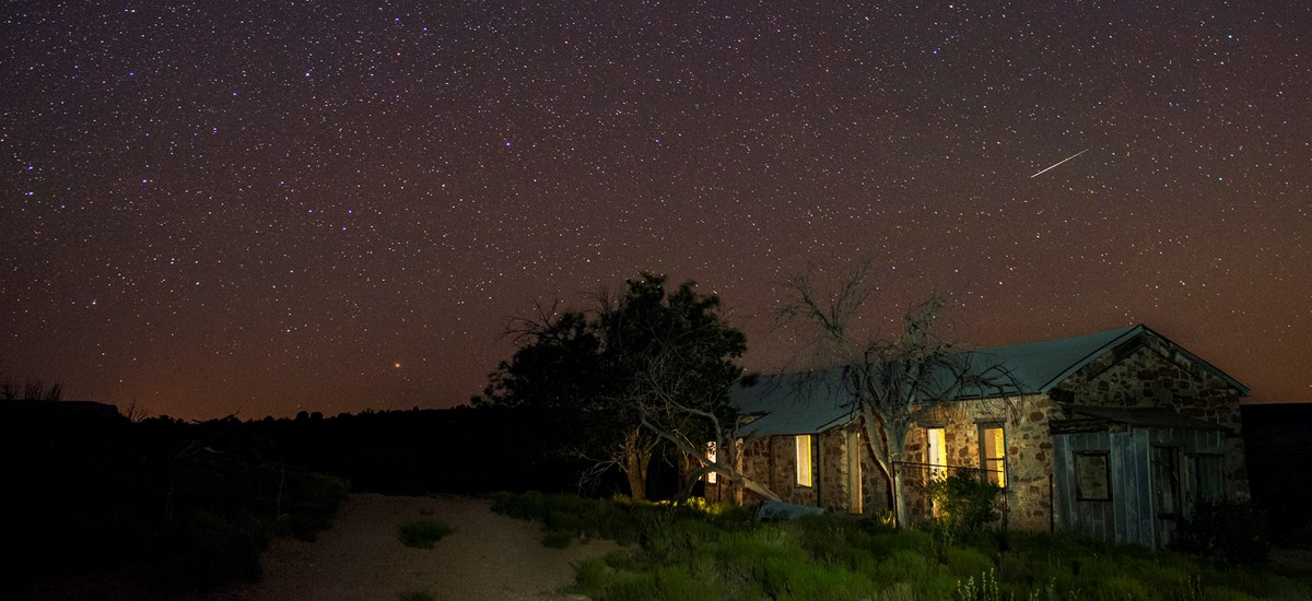 Stars and a shooting star above the historic bunkhouse ruin